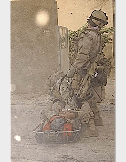 A US Soldier helping his mate back to the first aid post.